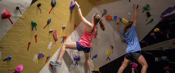 Students bouldering on a rock climbing wall.